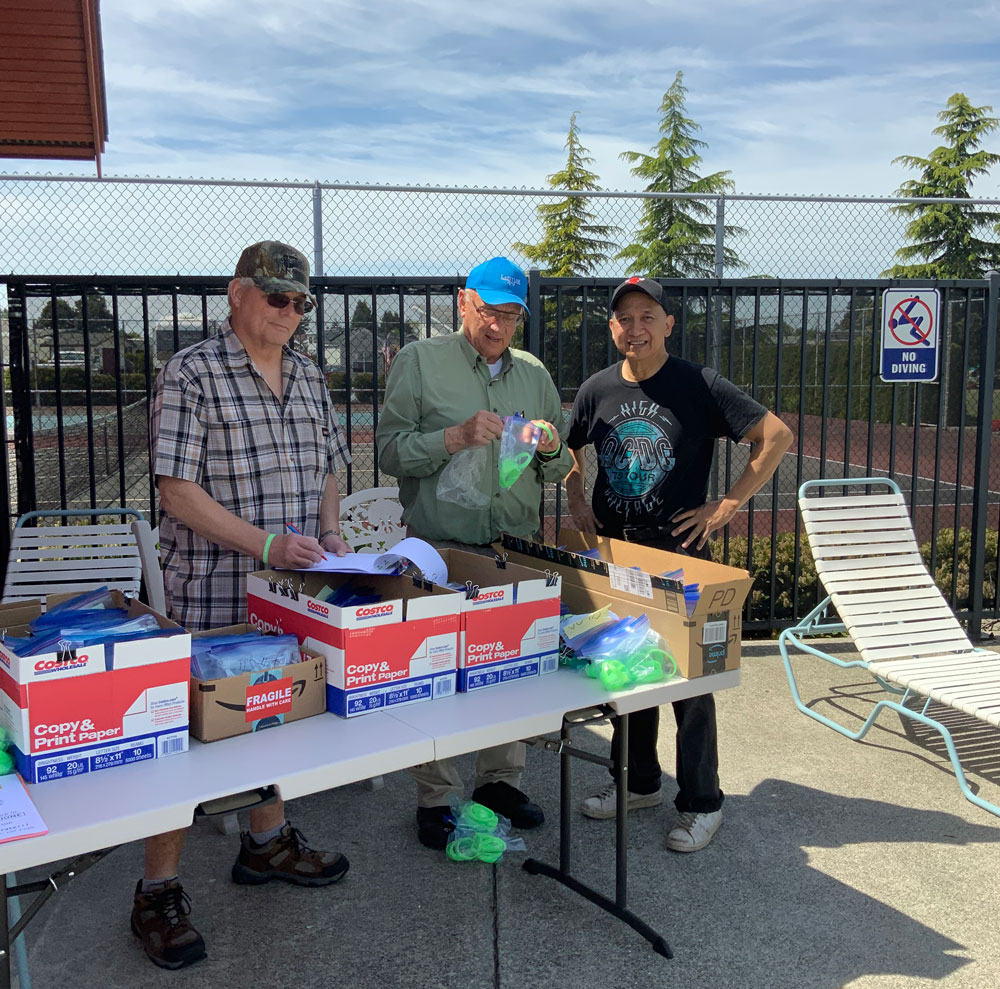 Volunteers distribute green bracelets to residents using the pool